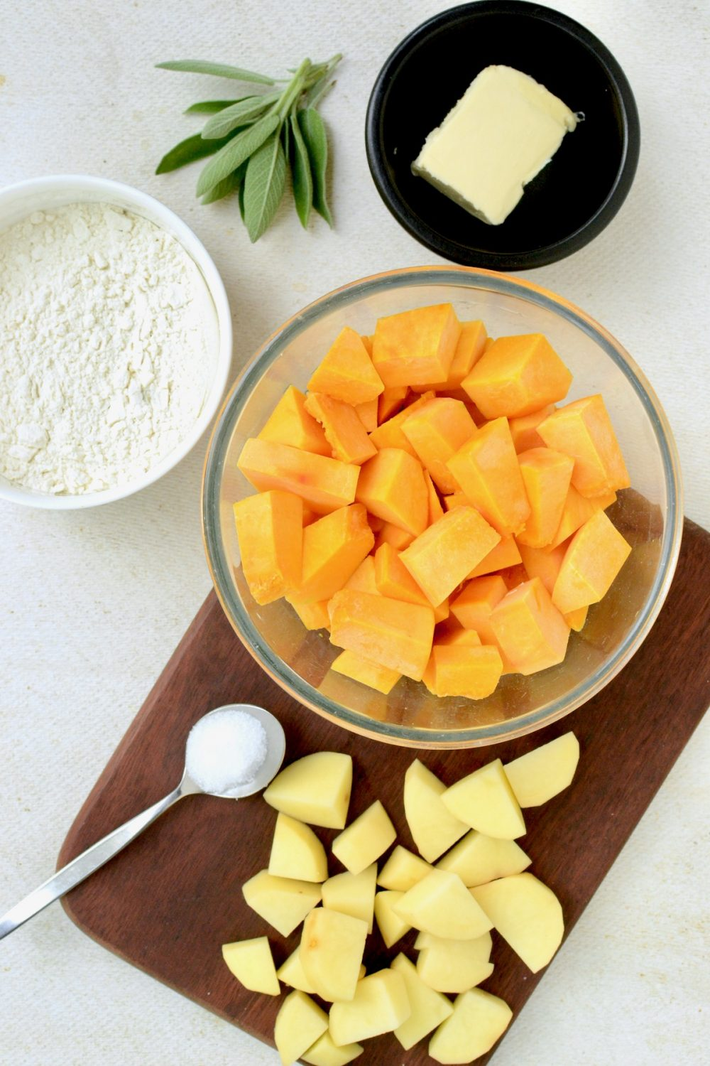 A bowl with cubes of pumpkin, next to a choppinf board with poato cubes, a bowl of flour, a square of vegan butter and a sprig of sage.