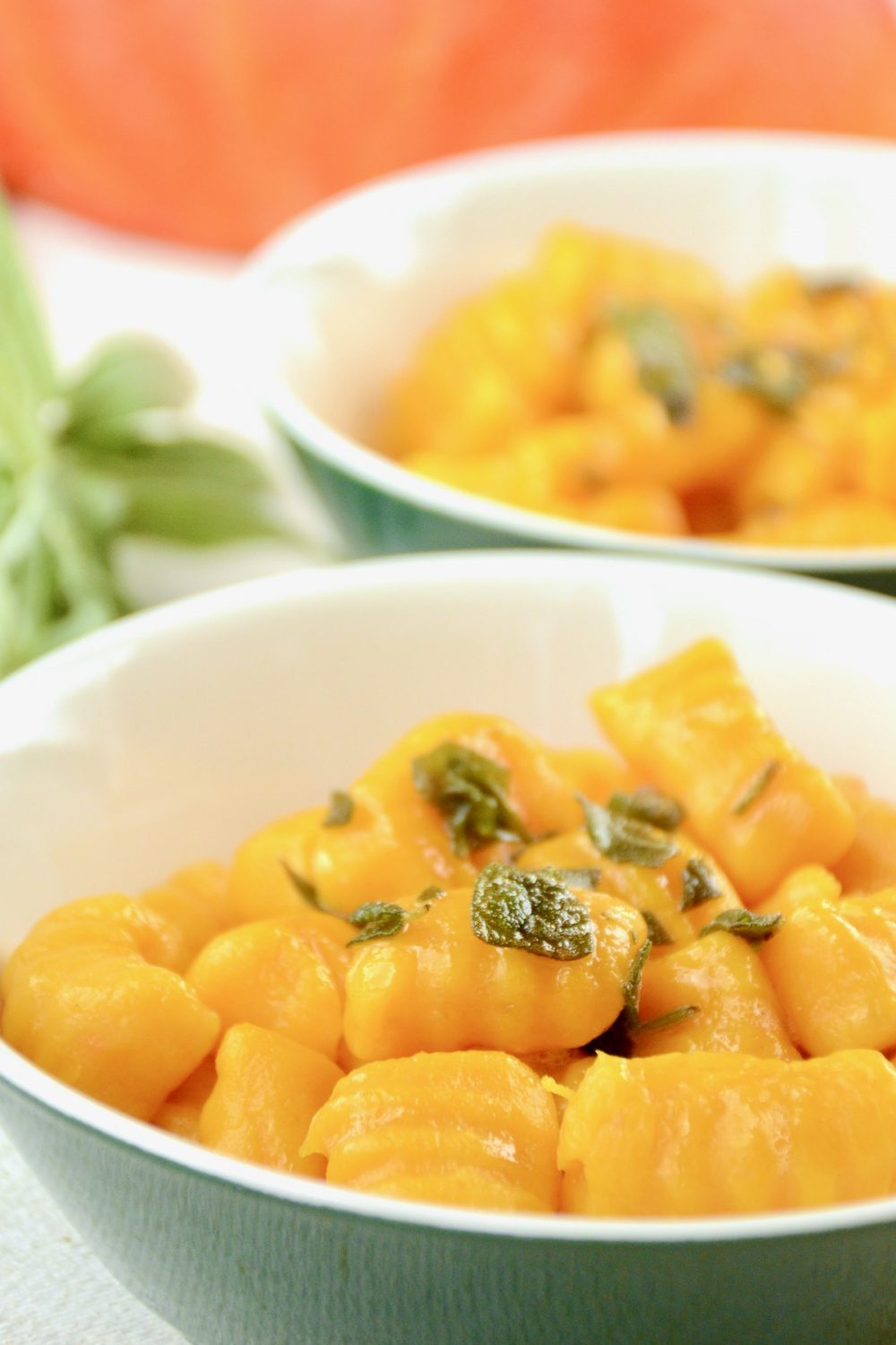 Two bowls containing pumpkin gnocchi with the bright orange skin of a squash in the background.