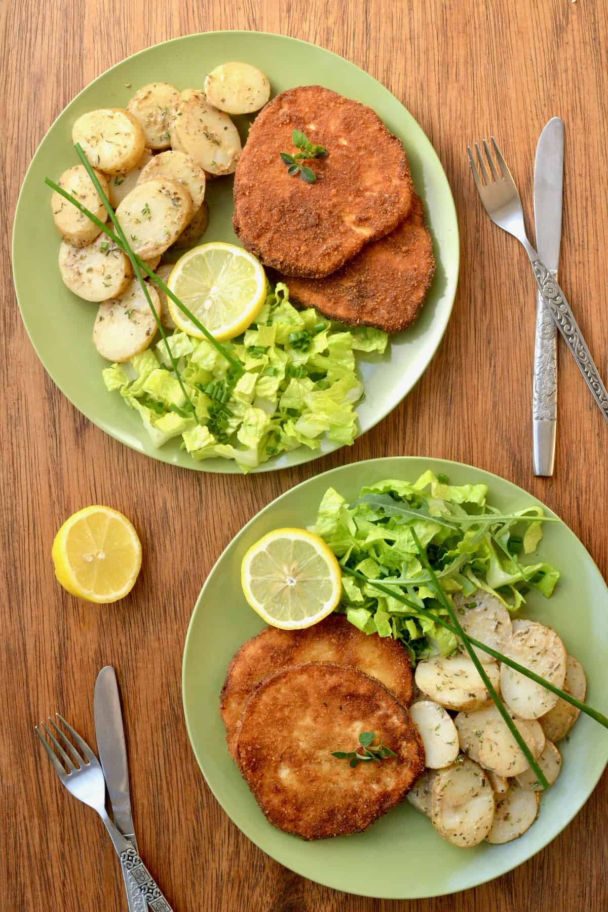 Two green plates with a serving of two fried schnitzels, herby potato salad and a green lettuce salad.