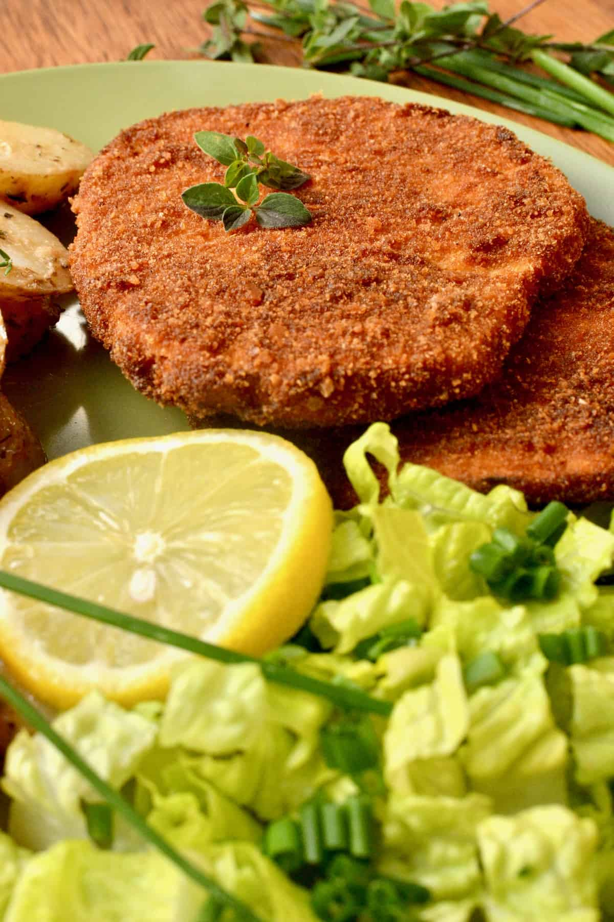 The dark golden breadcrumb crust of the schnitzel next to a slice of lemon and green salad.