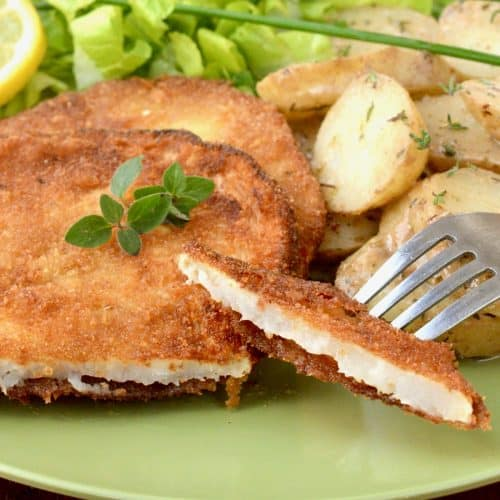 A bite of vegan schnitzel on a fork is lifted from a plate with potato salad on the side.