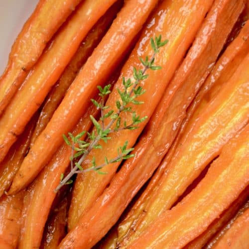 Glazed, roasted carrots and a twig of fresh thyme in a serving dish..
