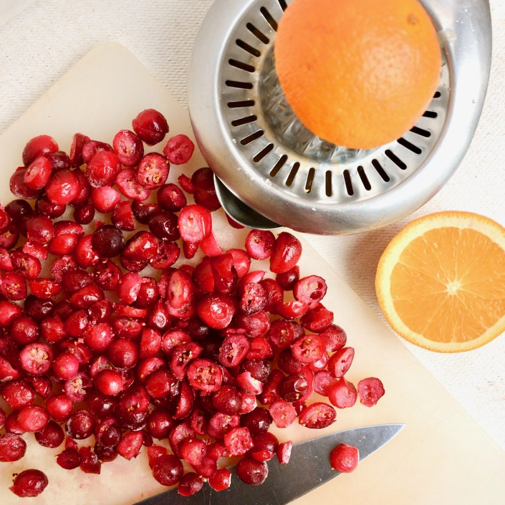 Chopping cranberries and juicing oranges.