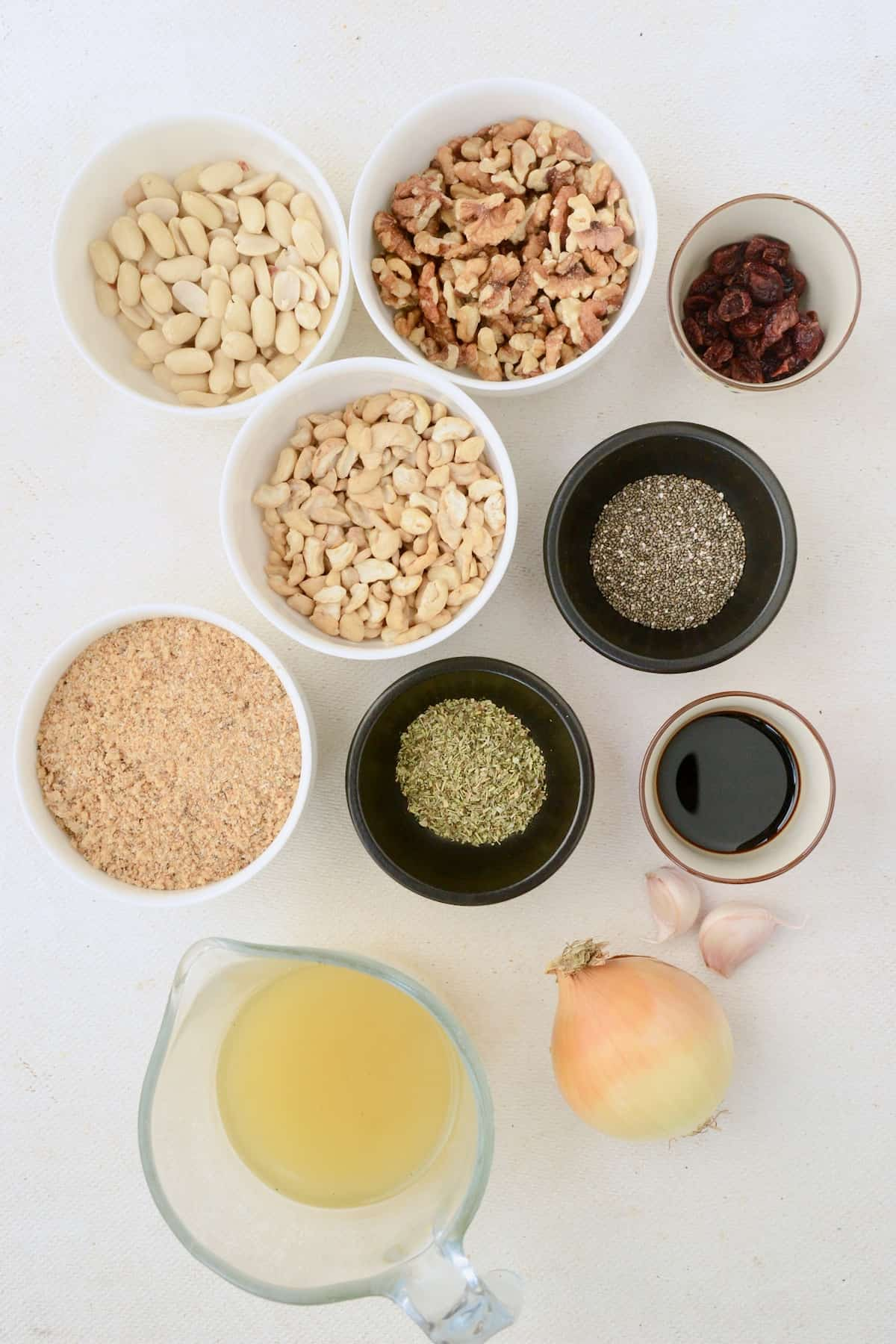 The ingredients for the nutroast recipe: Different types of nuts, breadcrumbs, an onion, some garlic, dried herbs, vegetable bouillon, soy sauce, chia seeds and dried cranberries.