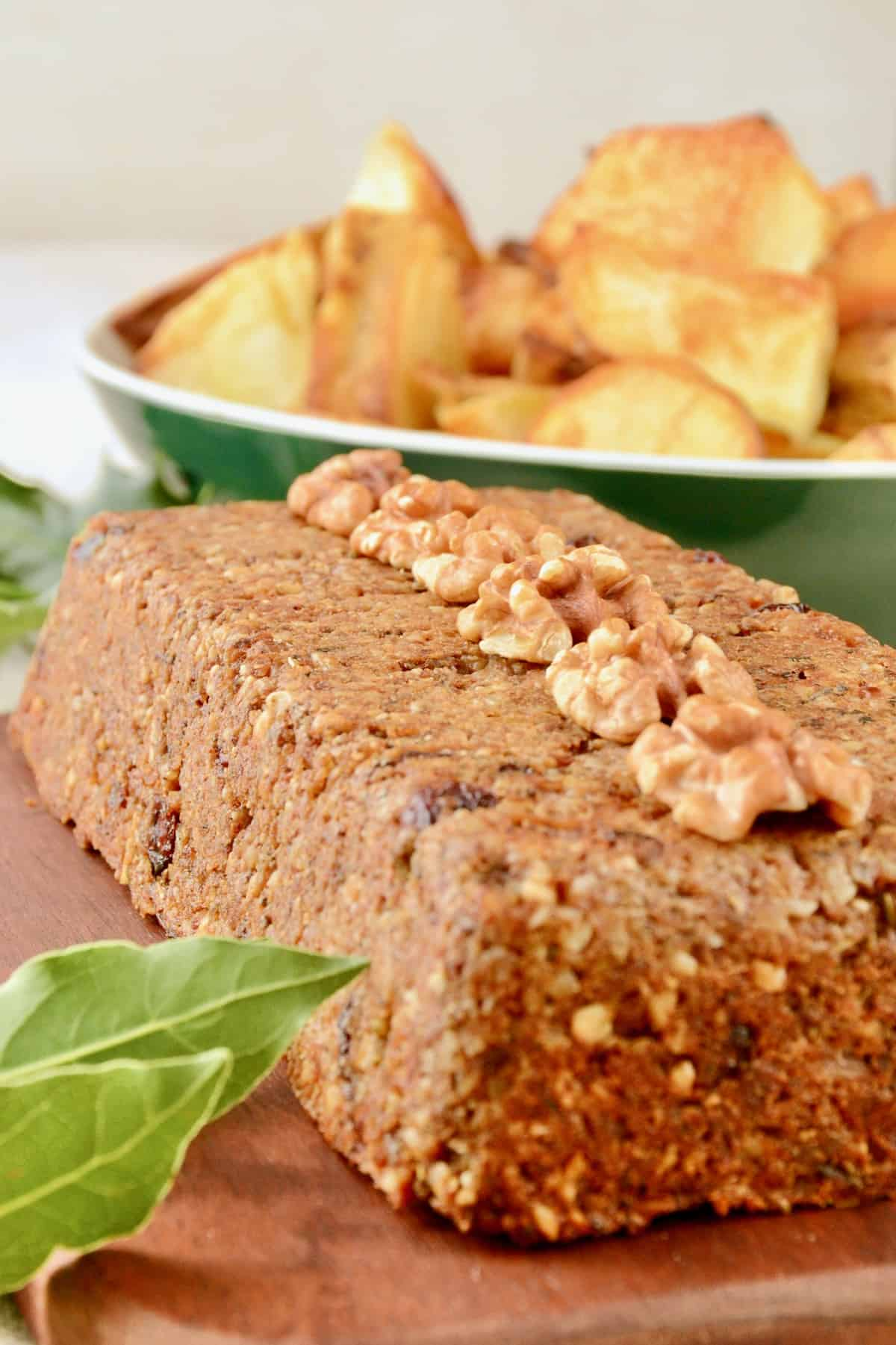 The whole loaf of nut roast served topped with walnut halves on a wooden board next to a dish full of baked potatoes.