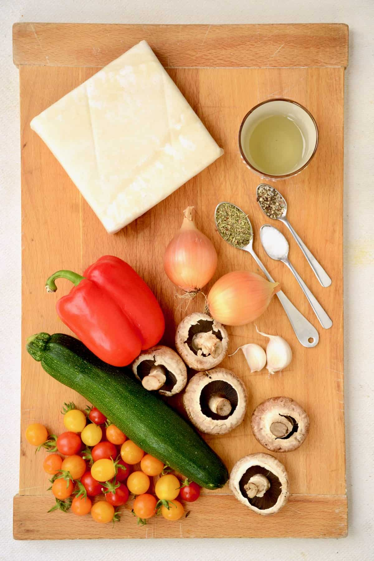A block of puff pastry, seasonings and vegetables on a wooden board.