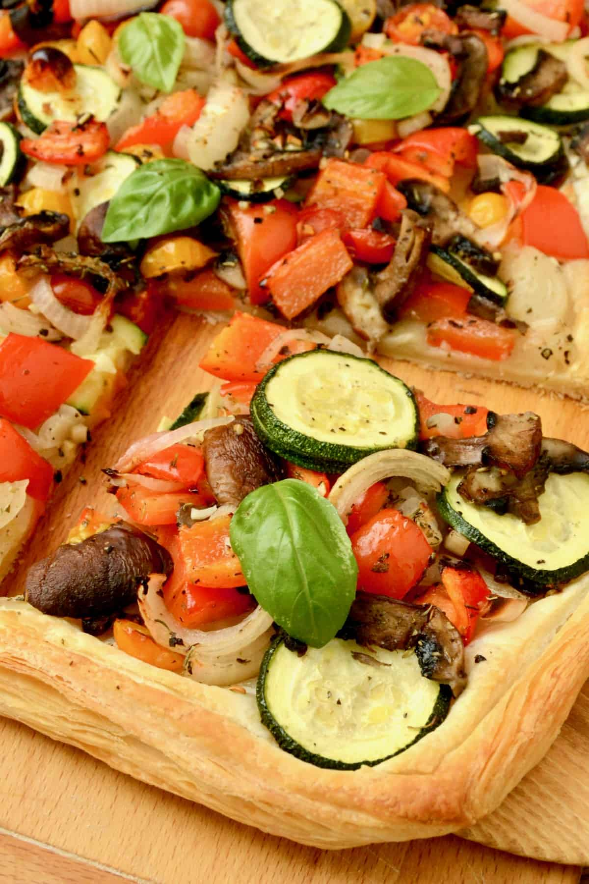 A slice of tart topped with zucchini, red pepper, onions, mushrooms.