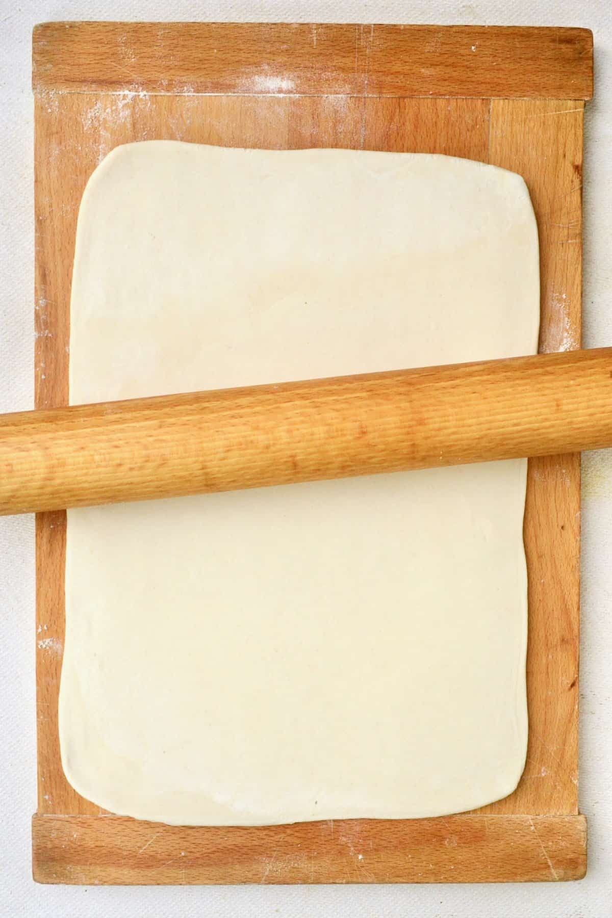 A rectangle of puff pastry being rolled out with a rolling pin.