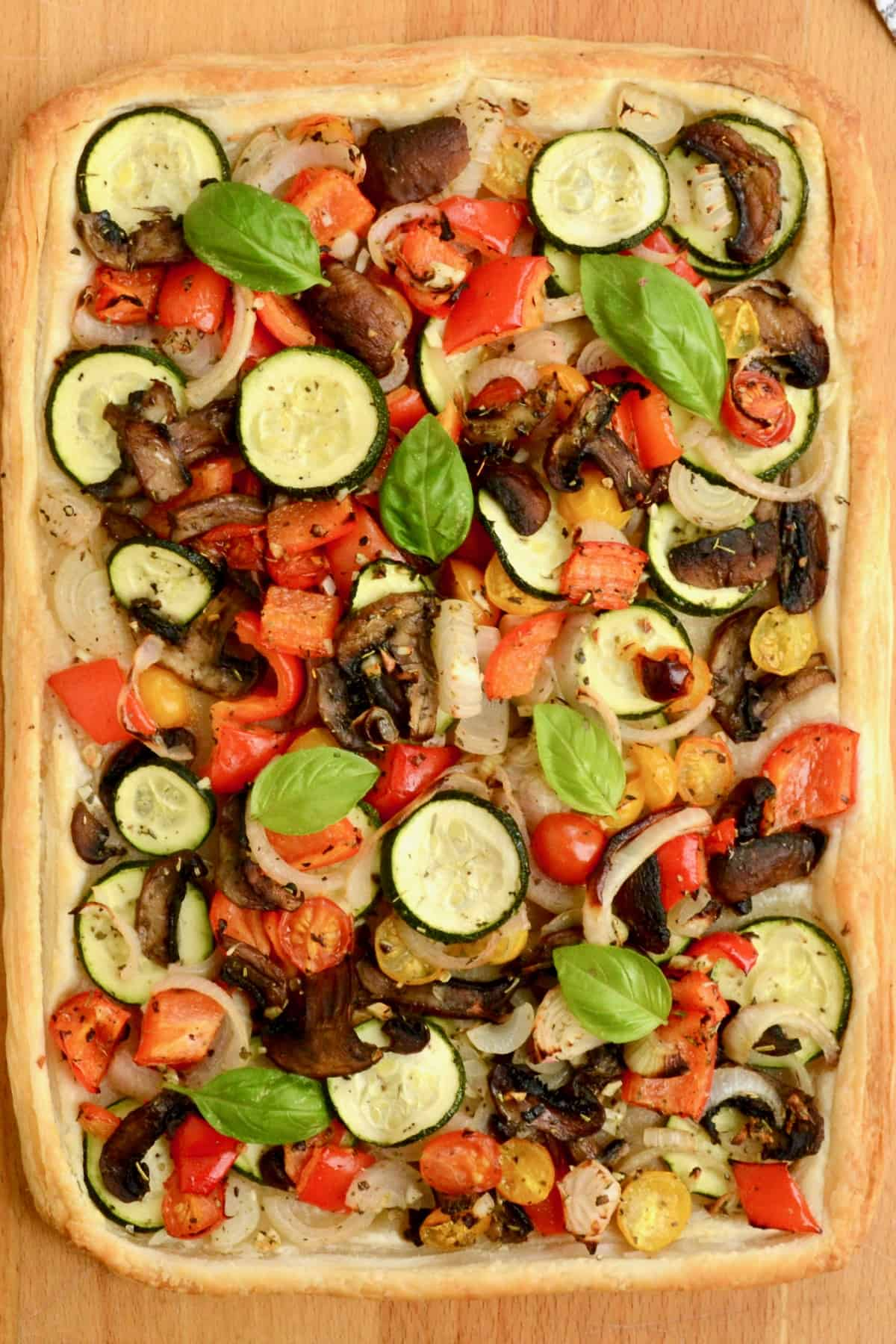 The cooked vegetable tart with colourful veggies and basil on top.