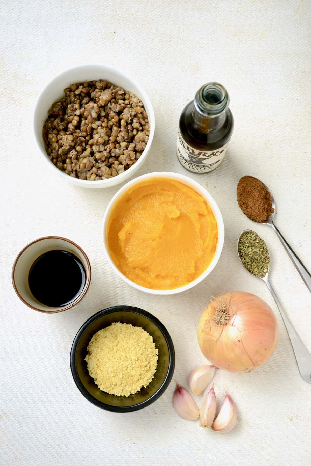 Ingredients on a white surface, bowls of pumpkin puree, lentils, nutritional yeast, soy sauce, a bottle of liquid smoke, onion, garlic and spices on spoons.