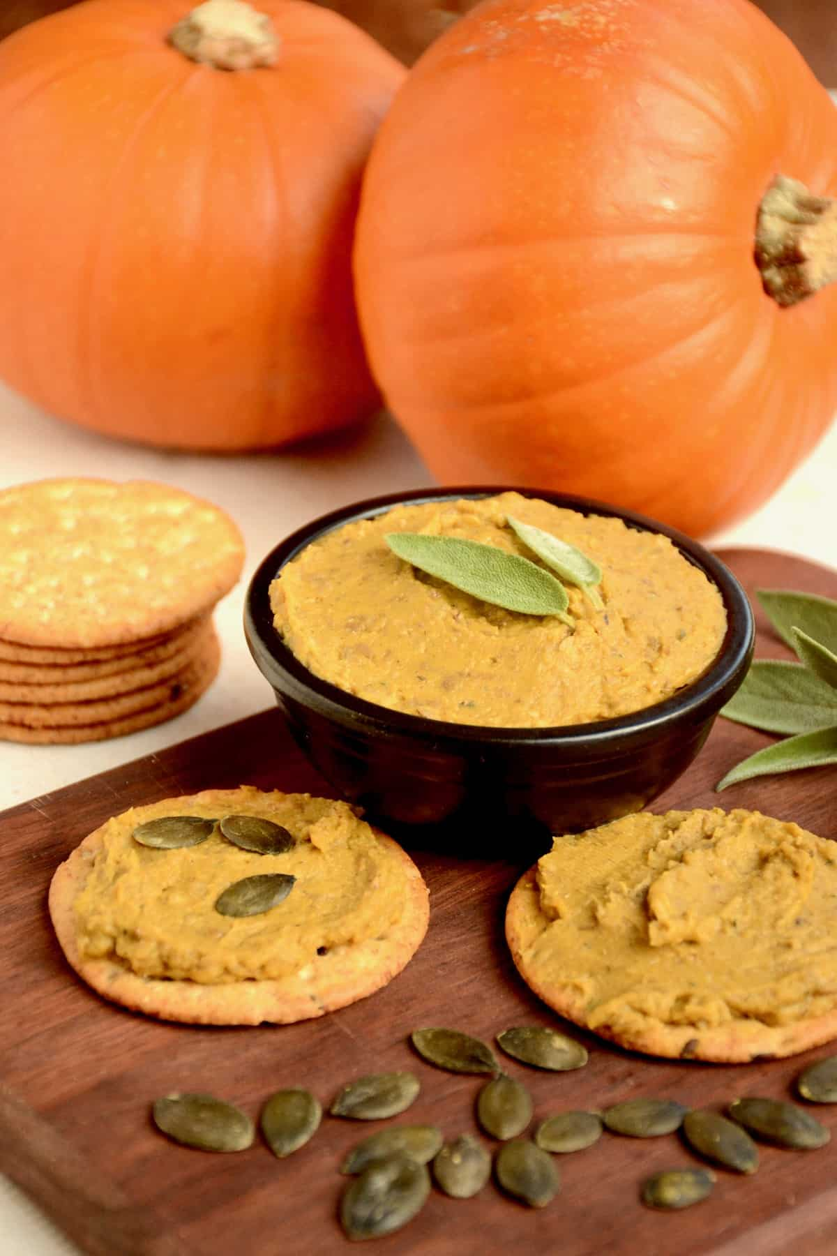 A wooden board with vegan pate and crackers and two small pumpkins in the background.