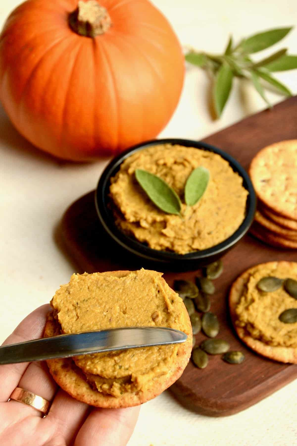 Spreading the pumpkin pate on a cracker.