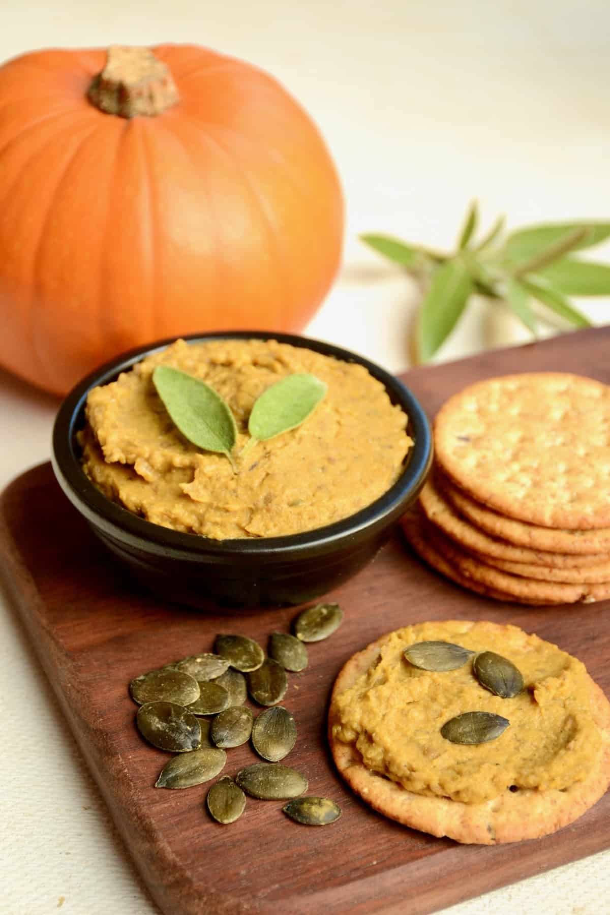 A black dish of pumpkin spreads next to a cracker topped with seeds.