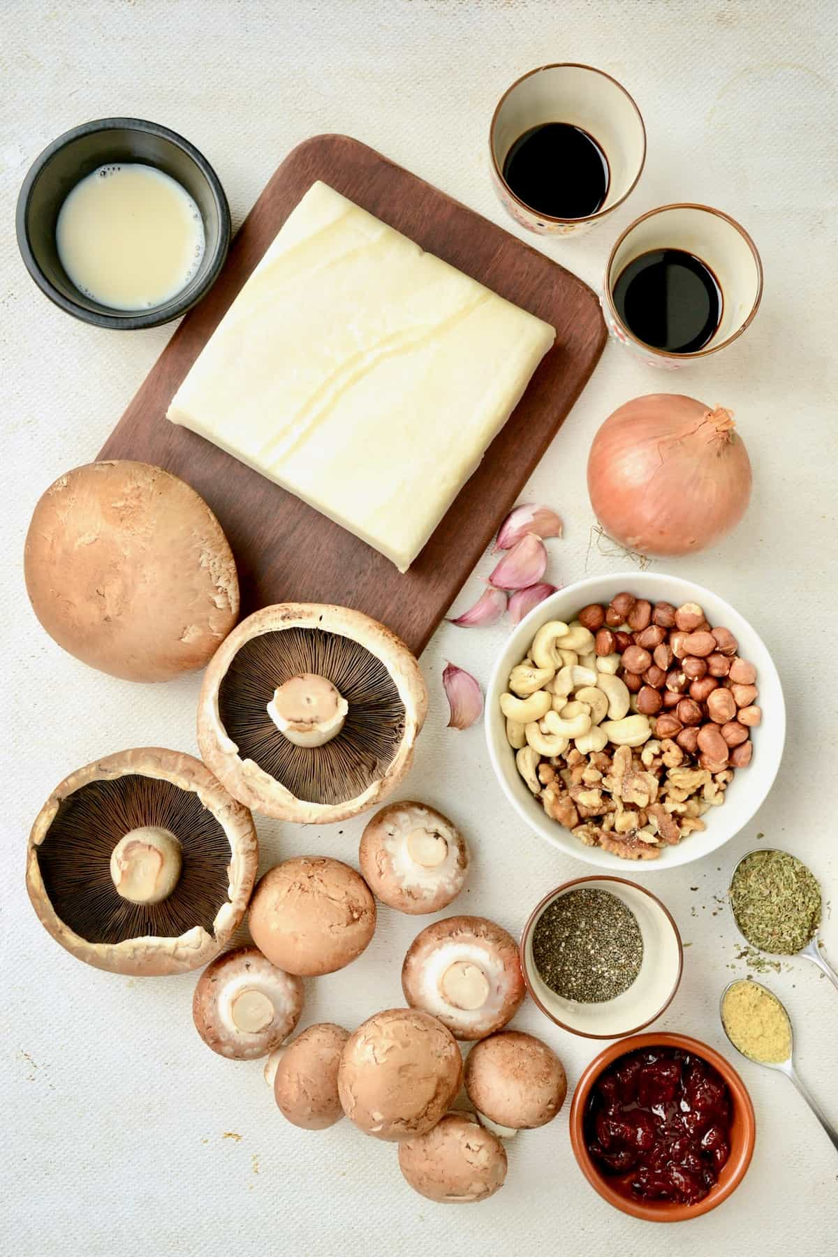 The ingredients for the mushroom wellington all laid out on a white surface.