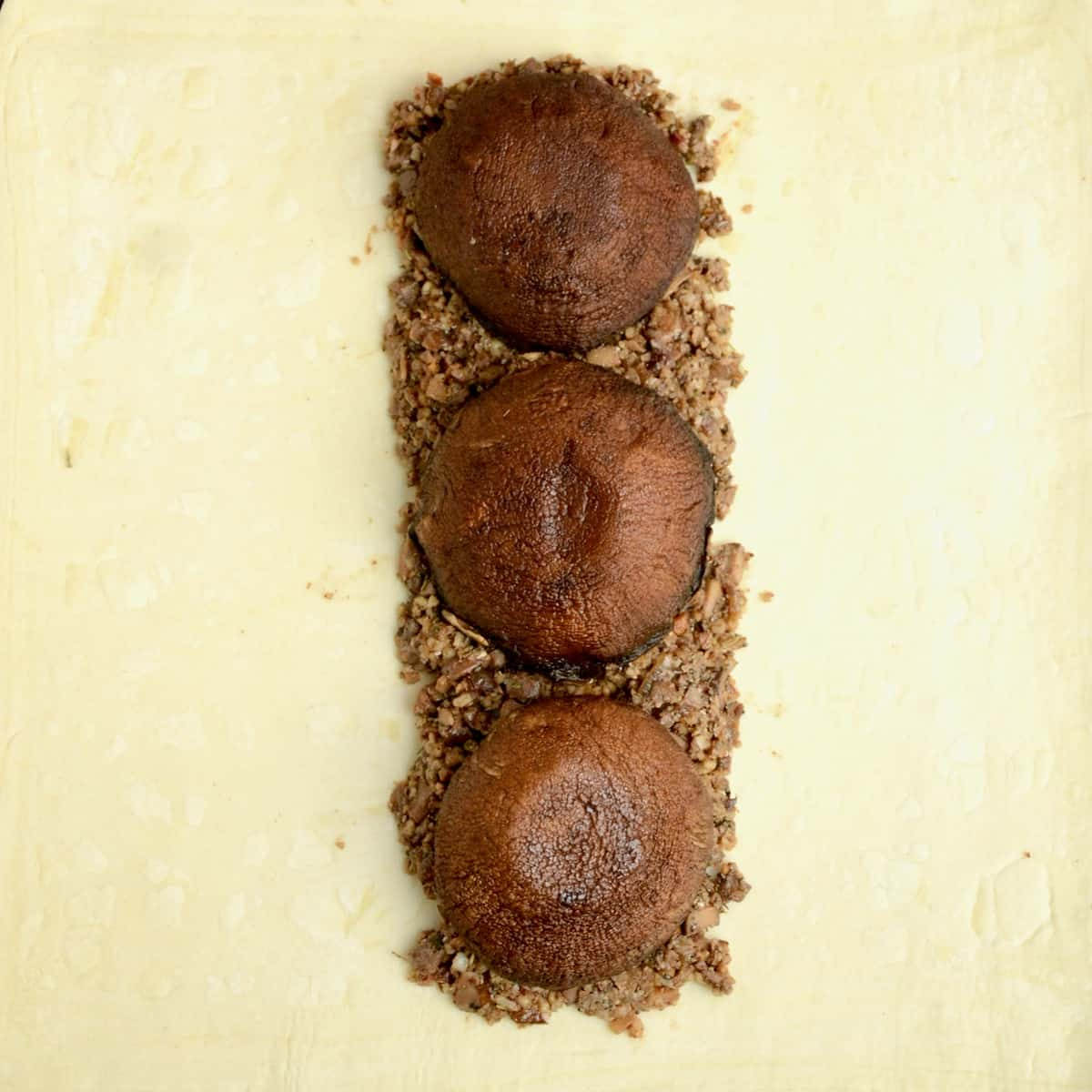 Large roasted mushrooms are placed in a line on top of the first layer of filling.