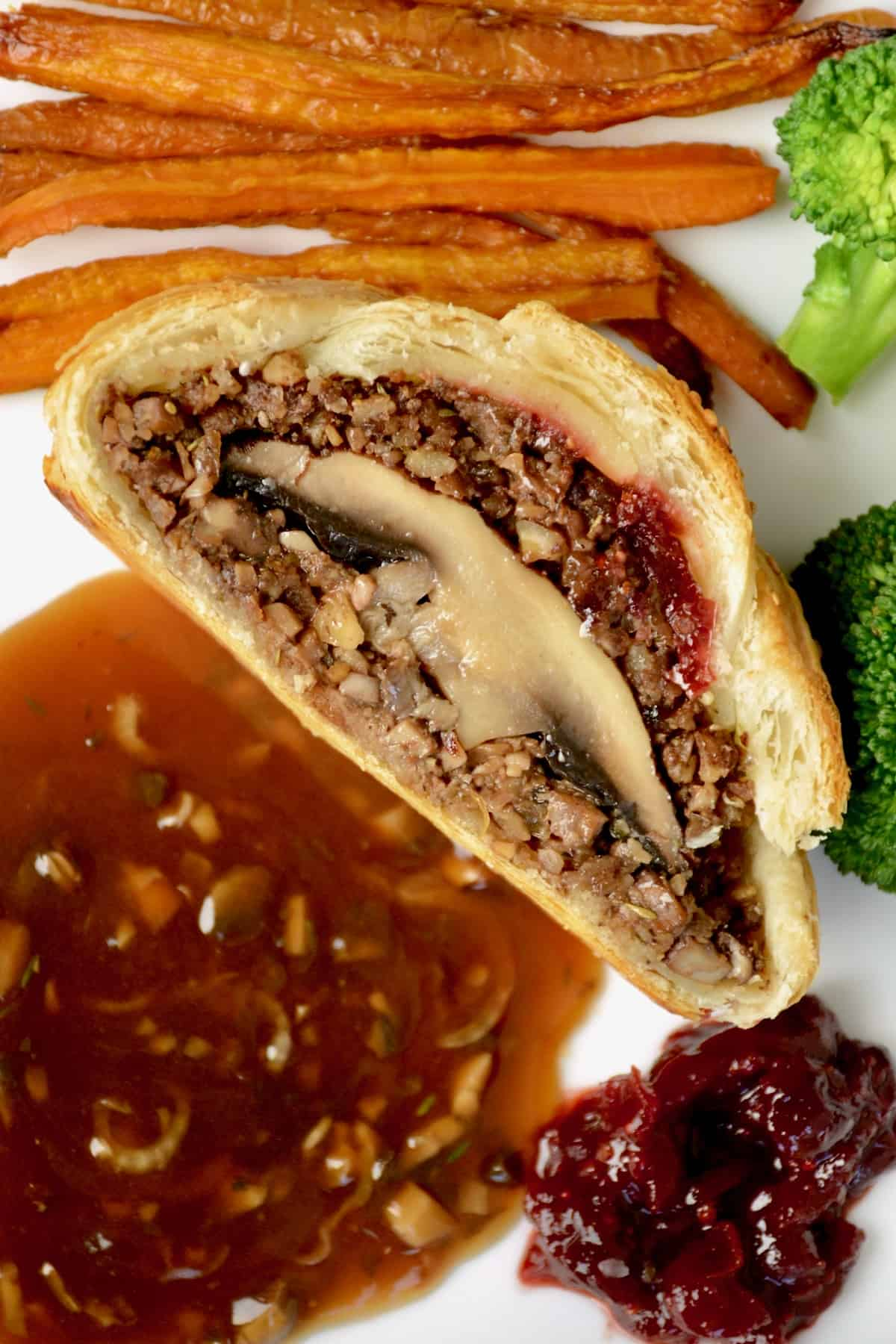 A slice of wellington revealing the cross section of a whole portobello mushroom inside, plated up with some vegetables, gravy and cranberry sauce.