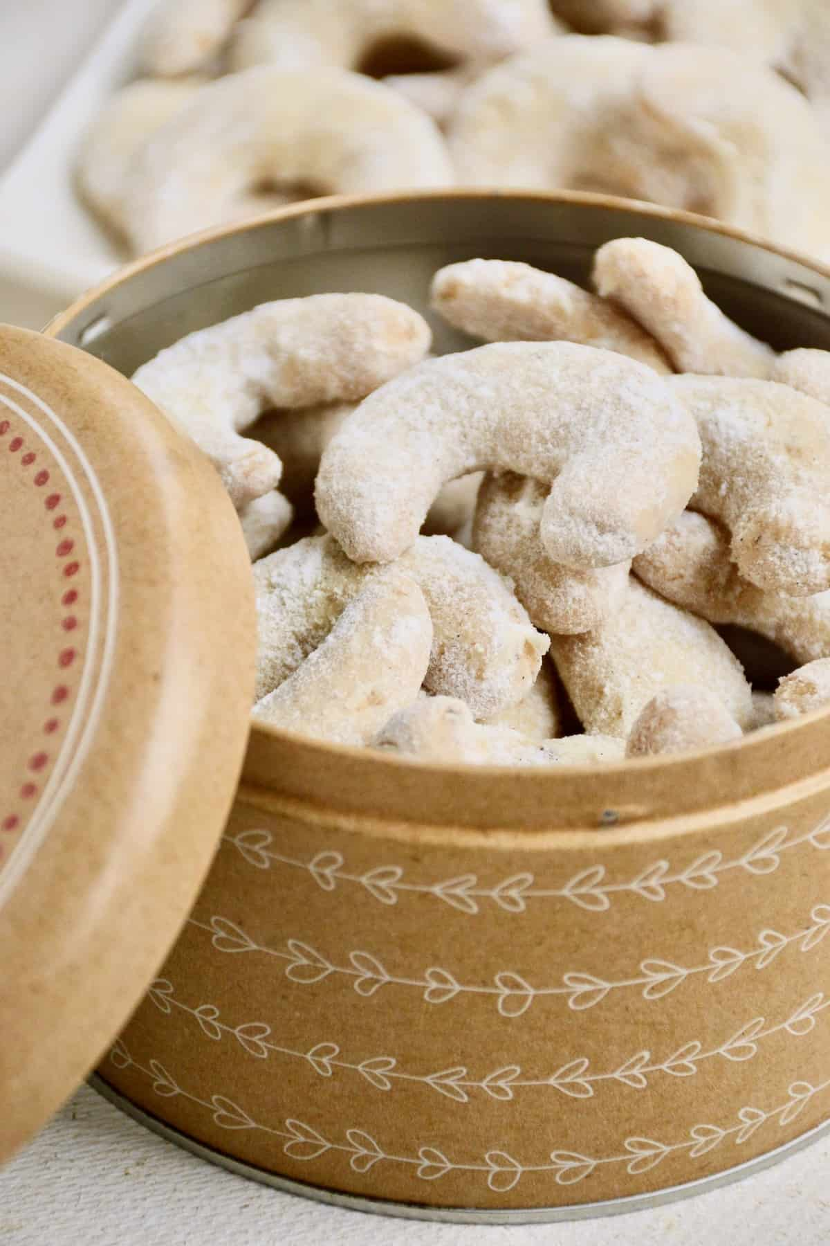 A tin full of crescent-shaped cookies coated in vanilla sugar.