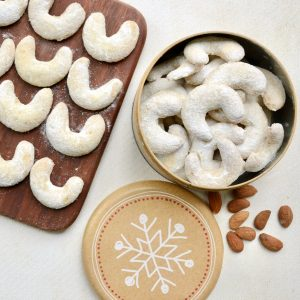Sugar dusted crescent cookies lined up in rows of four on a dark wooden board, next to a round tin full of more cookies. The light brown lid for the cookie tin is printed with a hand drawn giant snowflake.