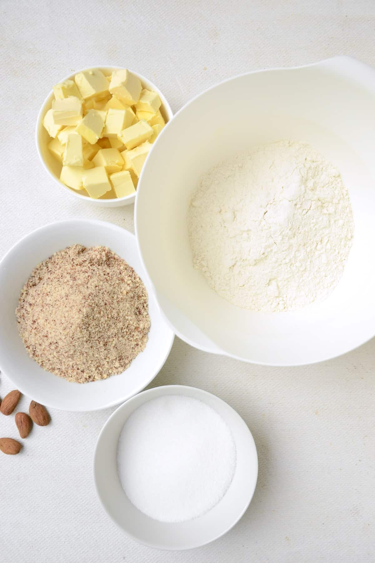 Dough ingredients for the vanilla crescent cookies: all-purpose flour, vegan butter cut into cubes, ground almonds, granulated sugar.