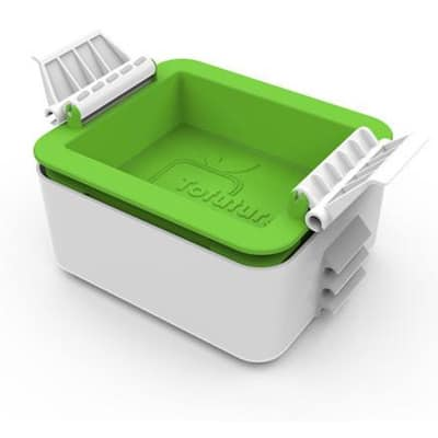 A white and green tofu press.
