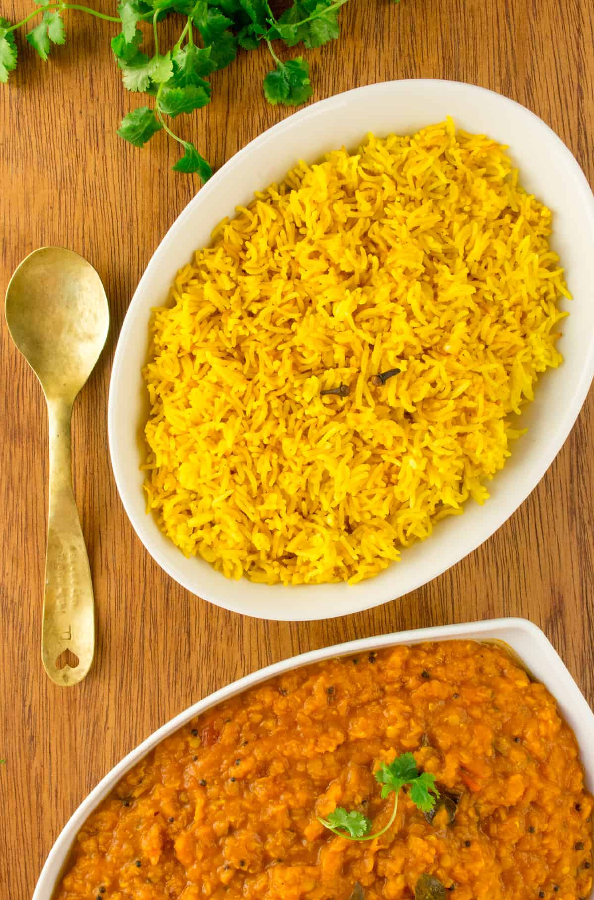 An oval dish of yellow rice, next to a brass spoon, dish of lentil dal and some coriander leaves.