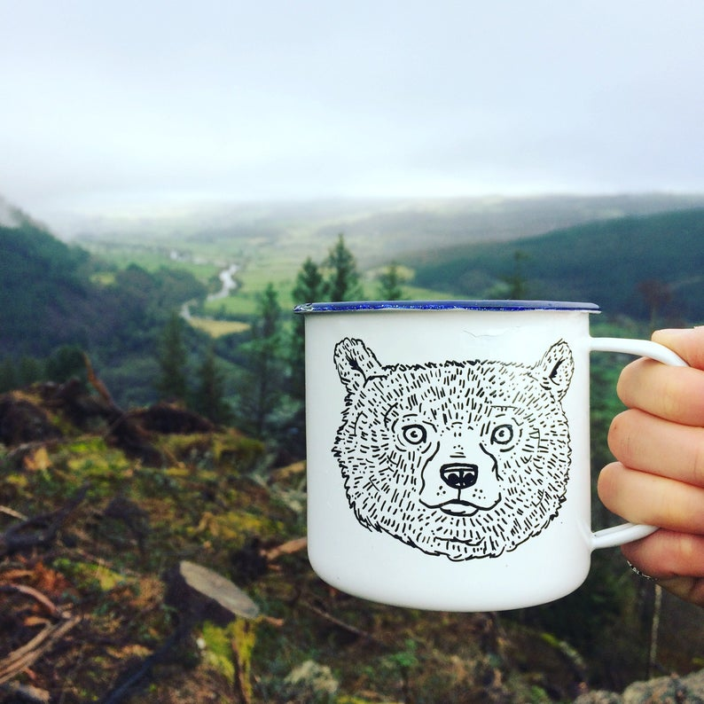 A hand holds up a white enamel mug with a bear drawing on it, in front of a forest landscape backdrop.