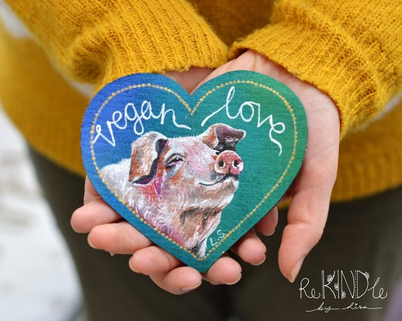 A heart-shaped denim patch with a painting of a pig and text 'vegan love'.