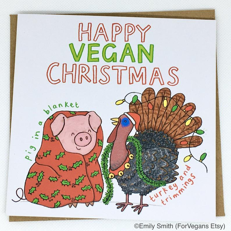 A gift card reading 'Happy vegan Christmas'. The drawn illustration shows a smiling pig wrapped in a warm blanket and a live turkey covered in christmas decorations. The drawings are labeled 'pig in a blanket' and 'turkey and trimmings'.