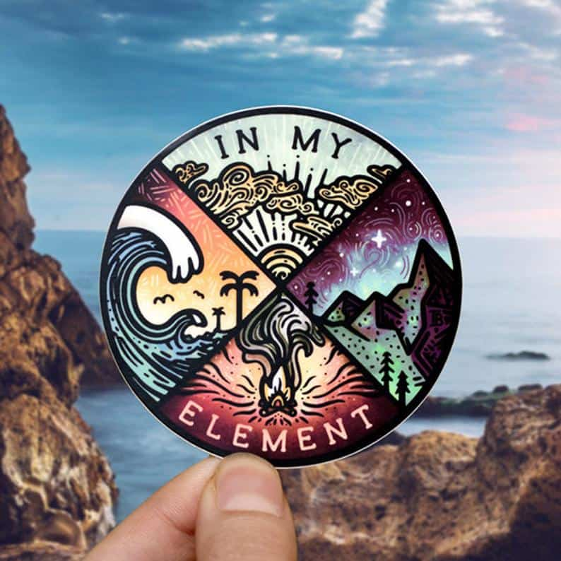 A sticker with a colourful illustration held up before a seaside landscape.