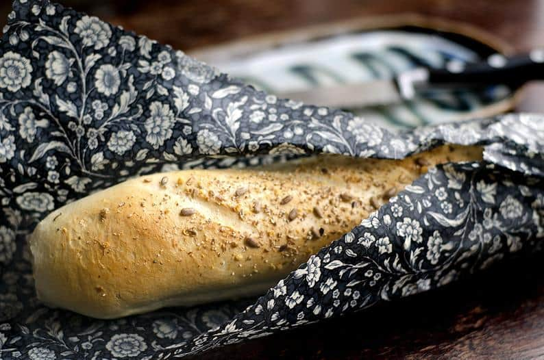 A baguette wrapped in a reuseable food wrapper.