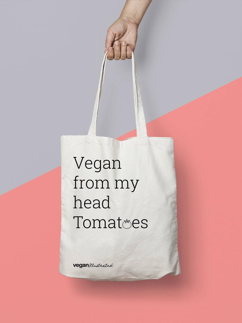 A tote bag with the slogan 'Vegan from my head Tomatoes'.