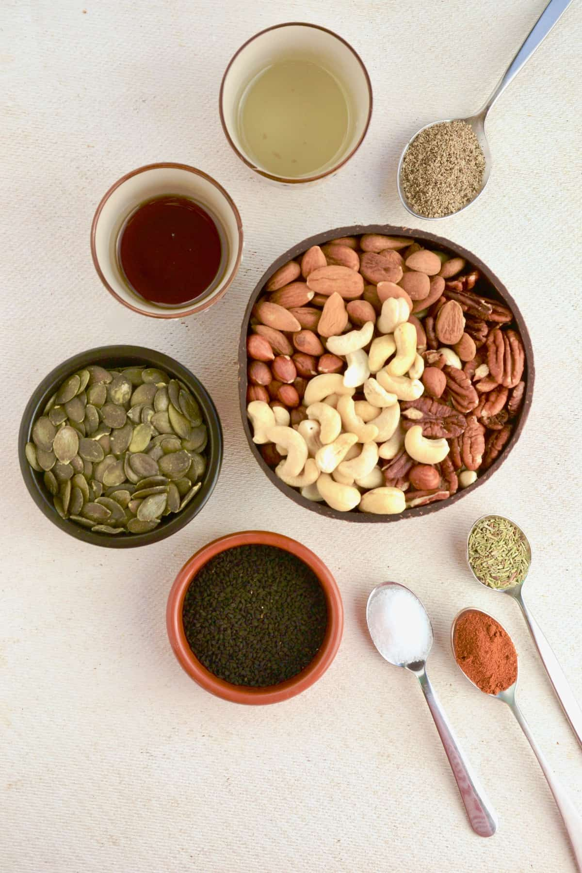 Bowls and spoonfuls of ingredients for spicy nuts.