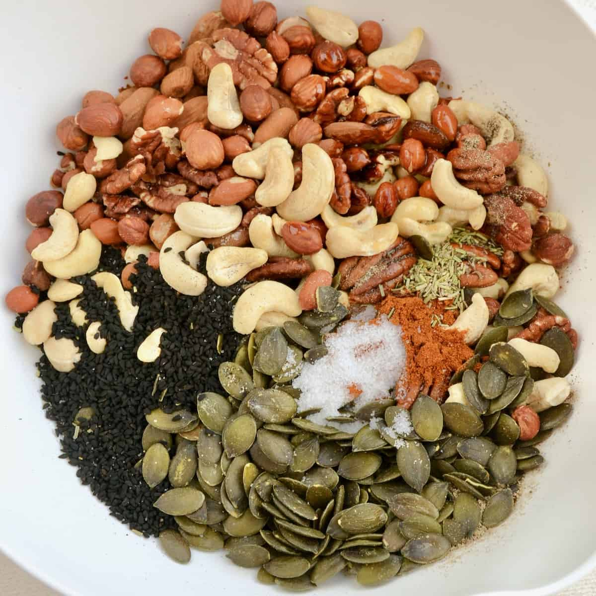 Nuts, seeds and seasonings in a white mixing bowl.