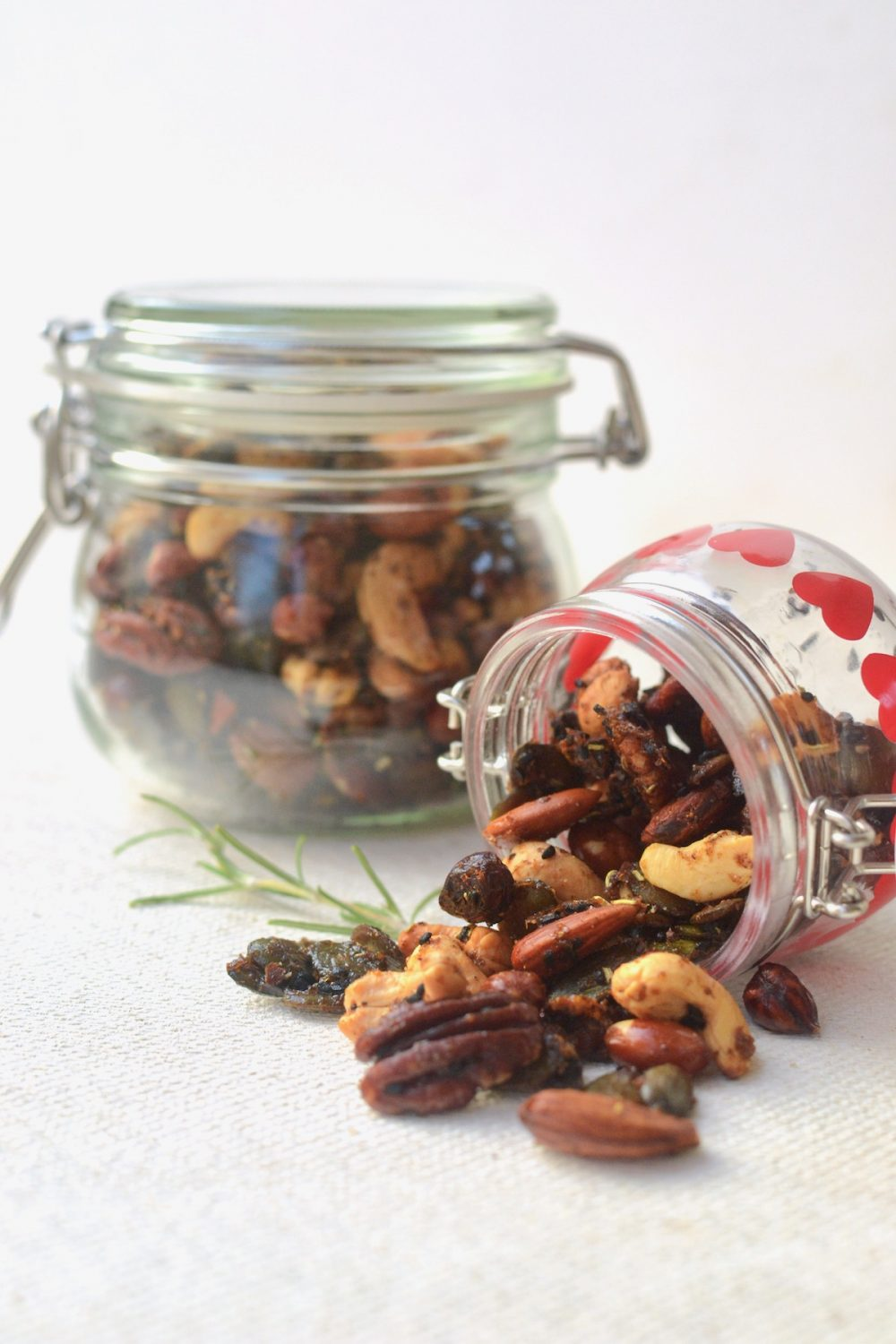 Two mason jars full of nuts, one on its side with nuts tumbling out.