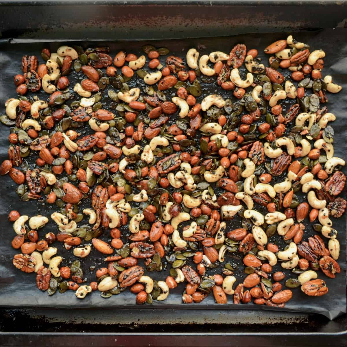 The nuts spread out on a lined baking tray.