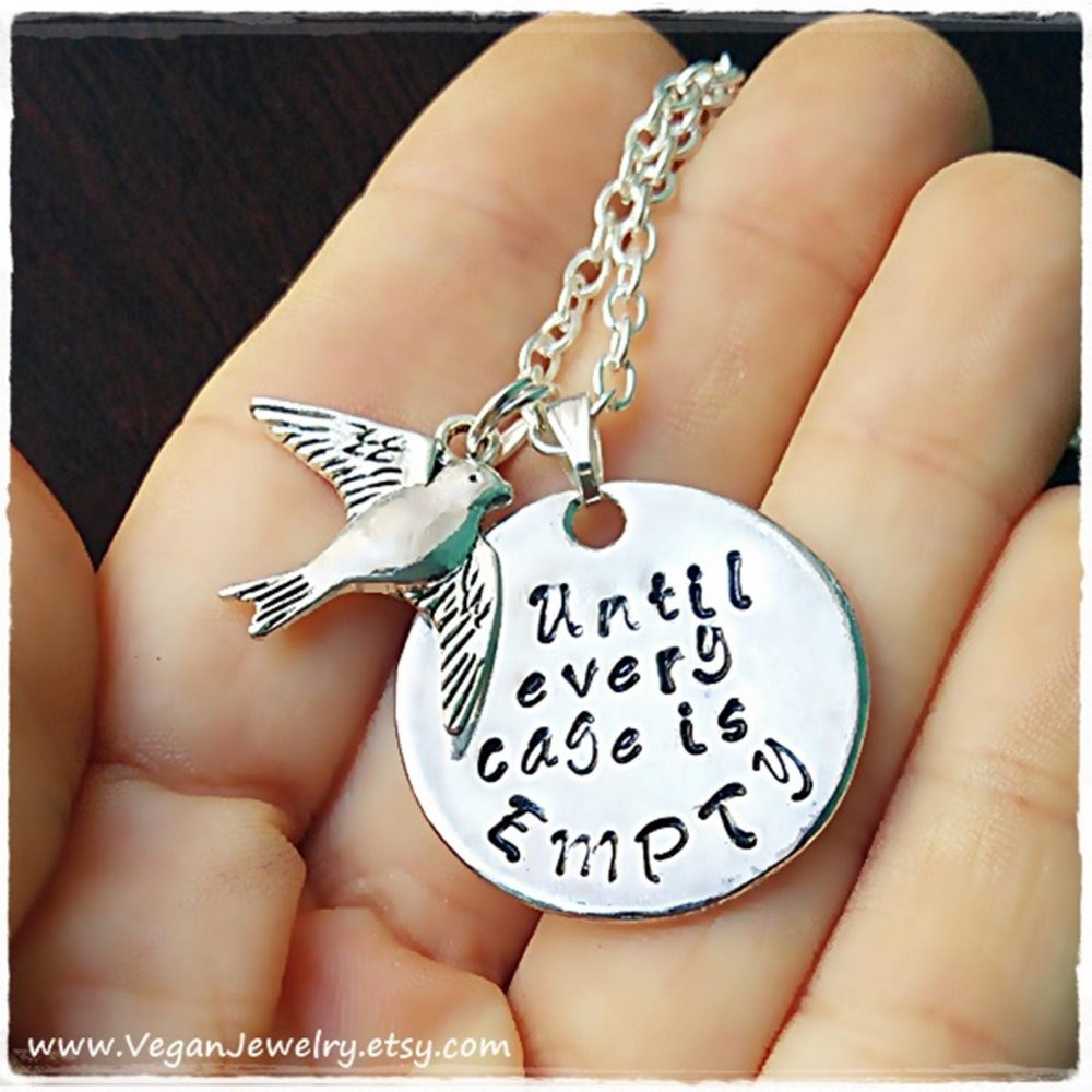 A necklace with two pendants. one is a silver dove, the other reads 'until every cage is empty'.