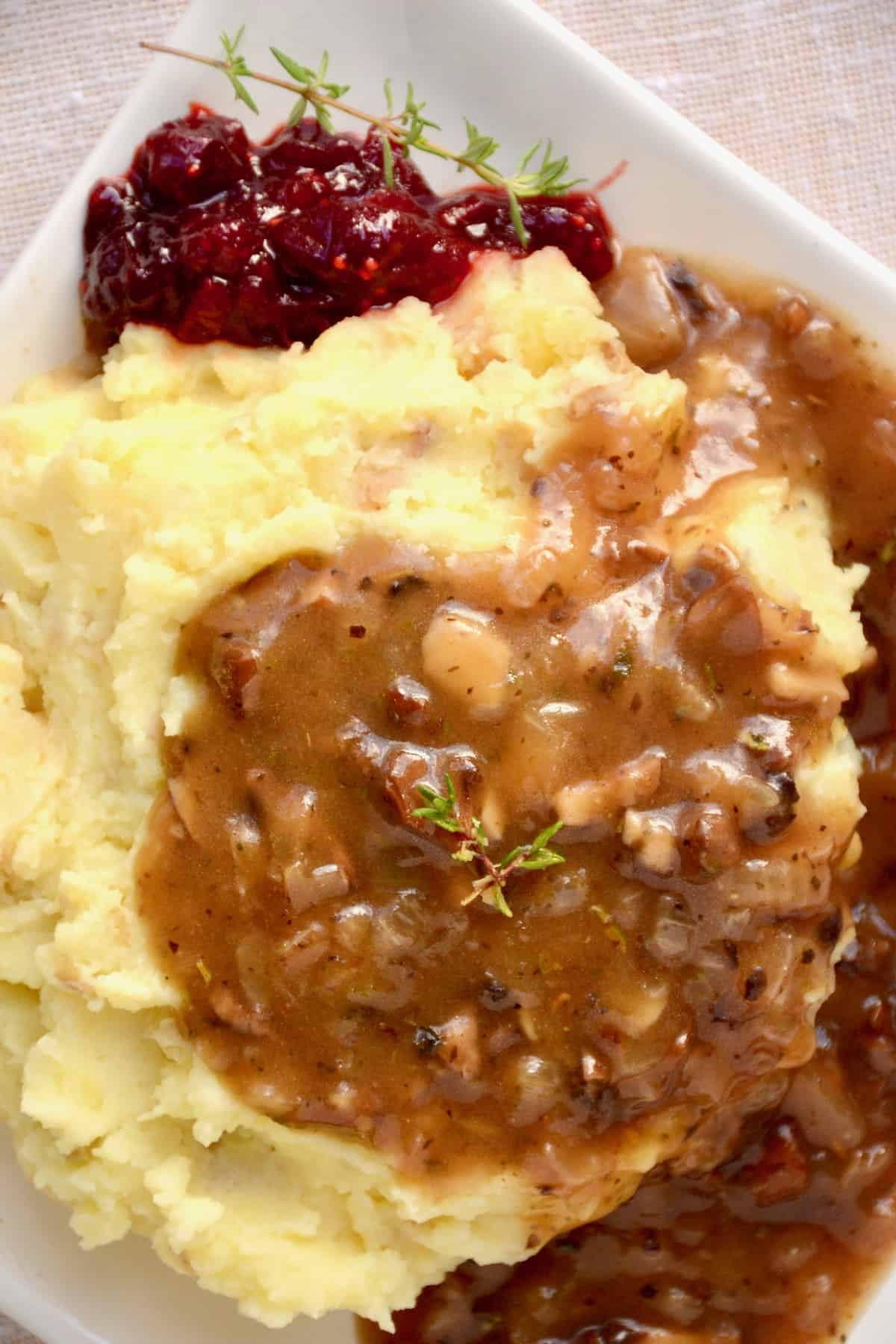 A plate of mashed potato with a generous serving of gravy.
