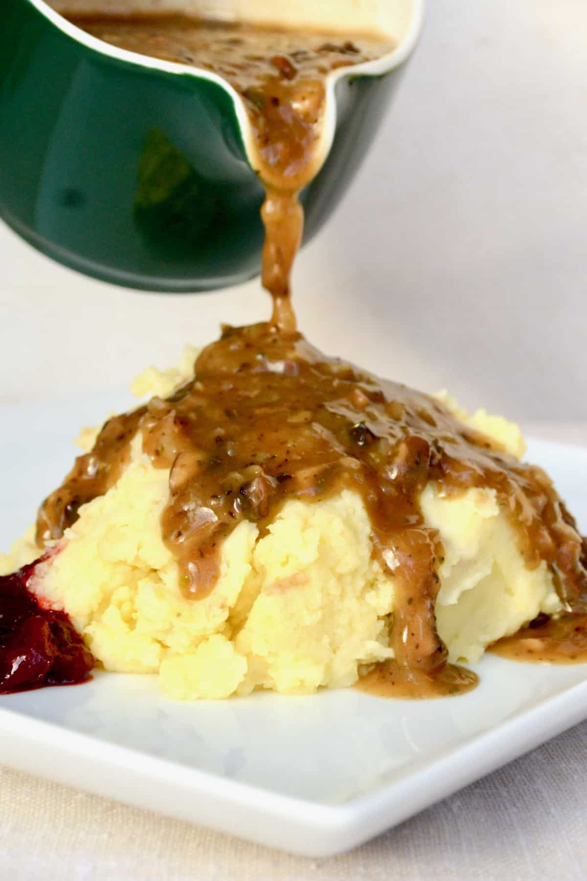 Gravy is poured and thickly flows down the side of mashed potato.