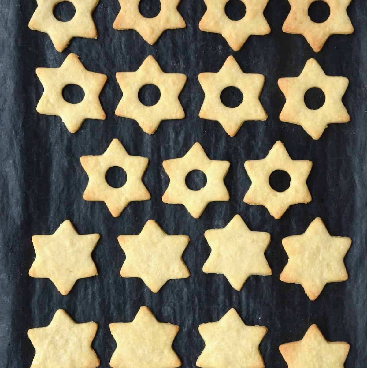 Baked, light brown star-shaped cookies on a baking tray.