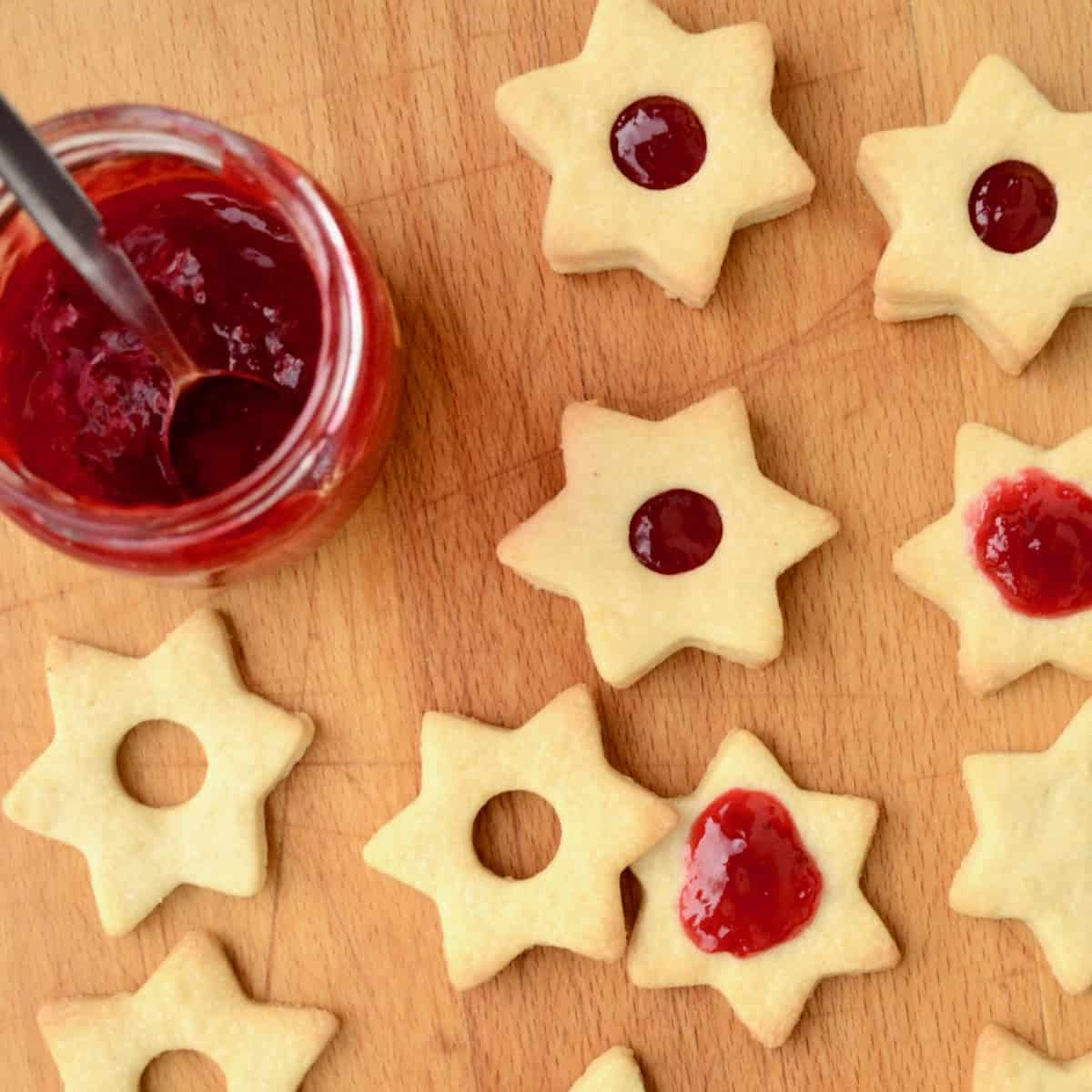 A jar of vibrant red jam. Pairs of cookies get stuck together with the jam.
