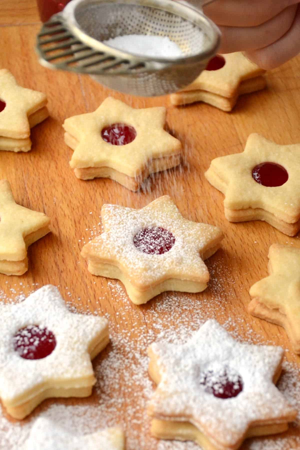 Icing sugar is dusted onto the cookies and melts on the jam that is exposed through the round openings in the cookie tops.