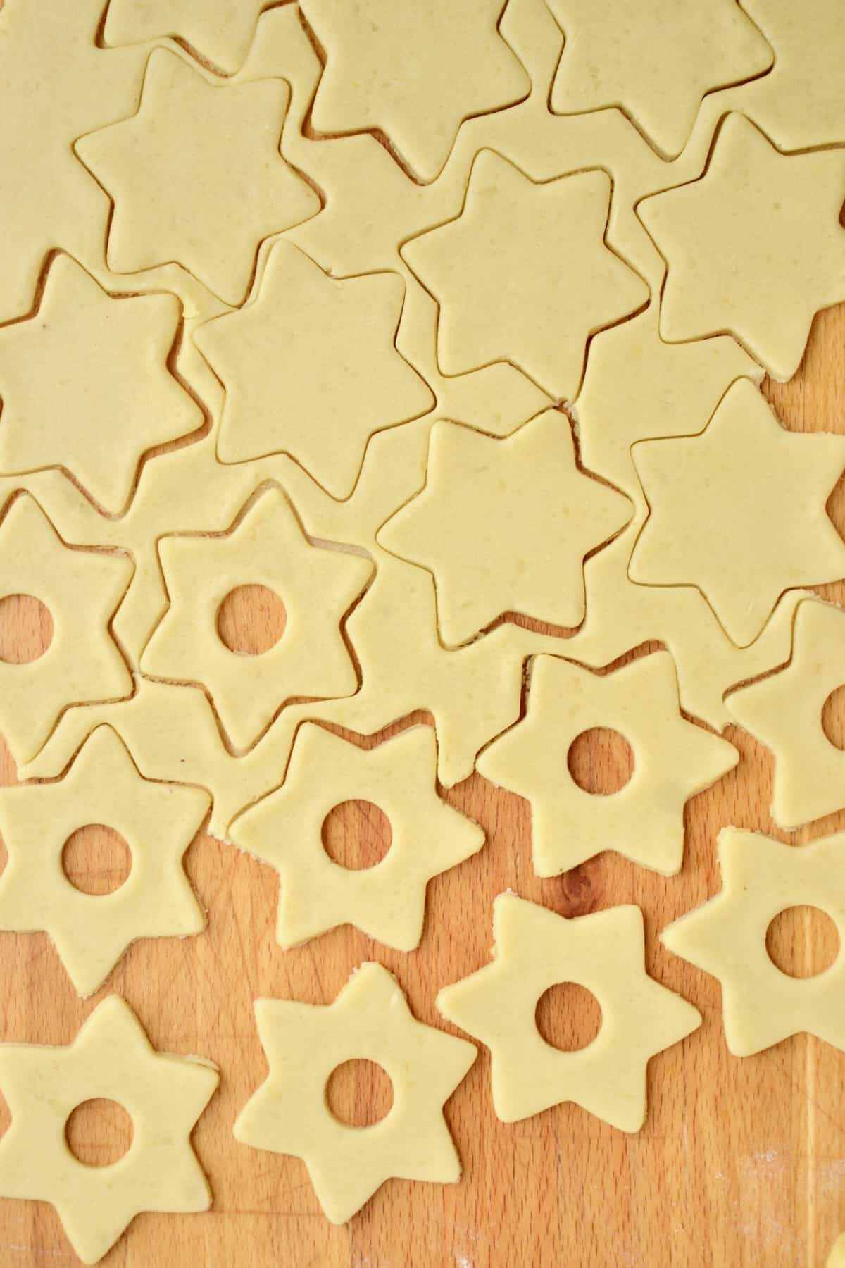 Star shapes cut from a sheet of cookie dough. Half of them have a round opening cut into their center. The dough cuttings between the shapes can be gathered and reused.