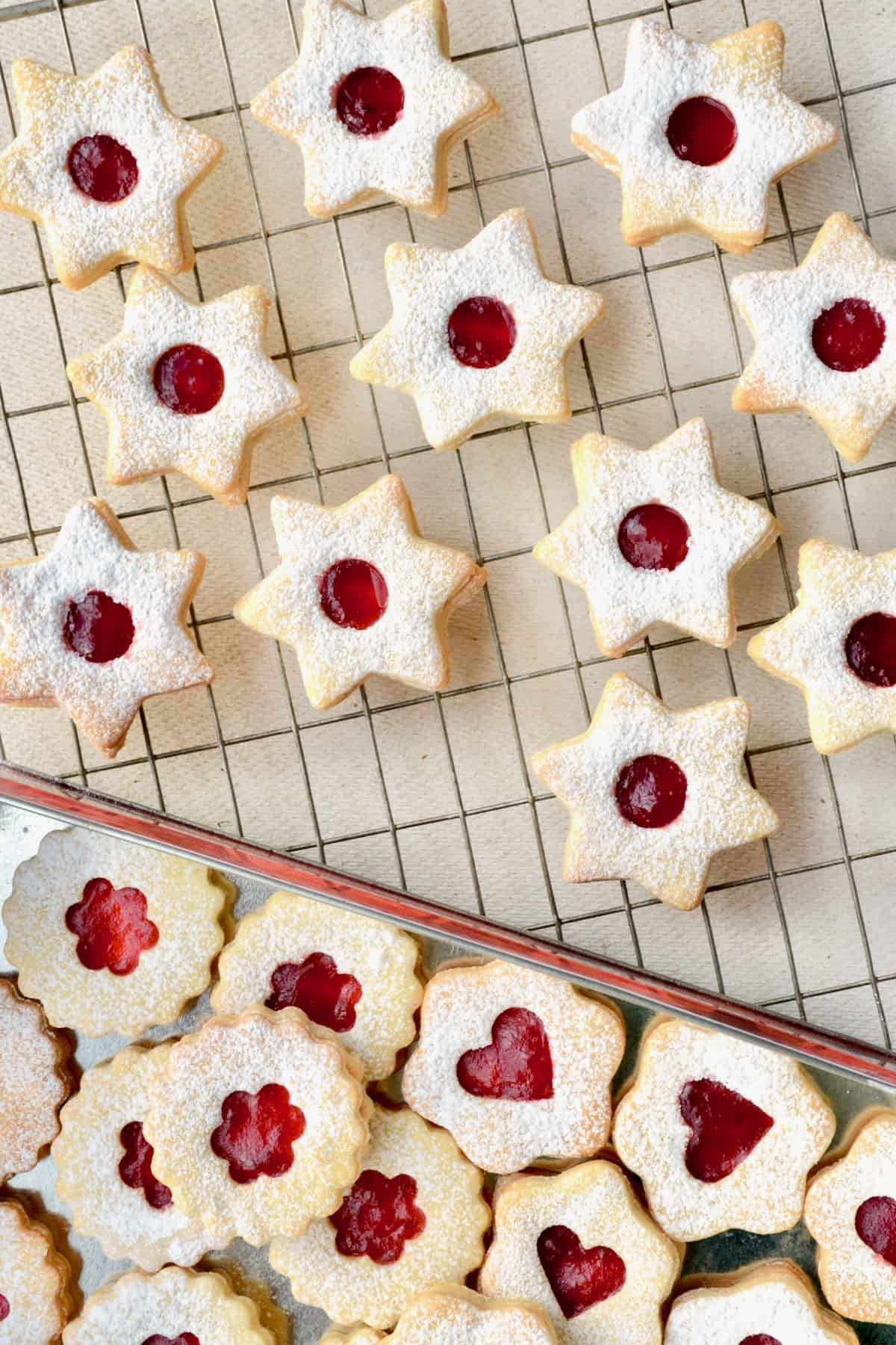 Linzer cookies can come in various different shapes: Stars, flowers, circles and more. But they all have a small opening in the top cookie layer, through which the jam filling can be observed.