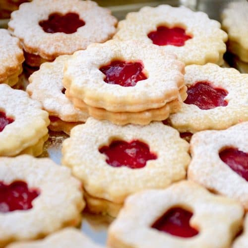 Linzer cookies are impressive double biscuits fillied with jam and dusted with icing sugar. A small central opening in the top reveals the jam that holds the two biscuits together.