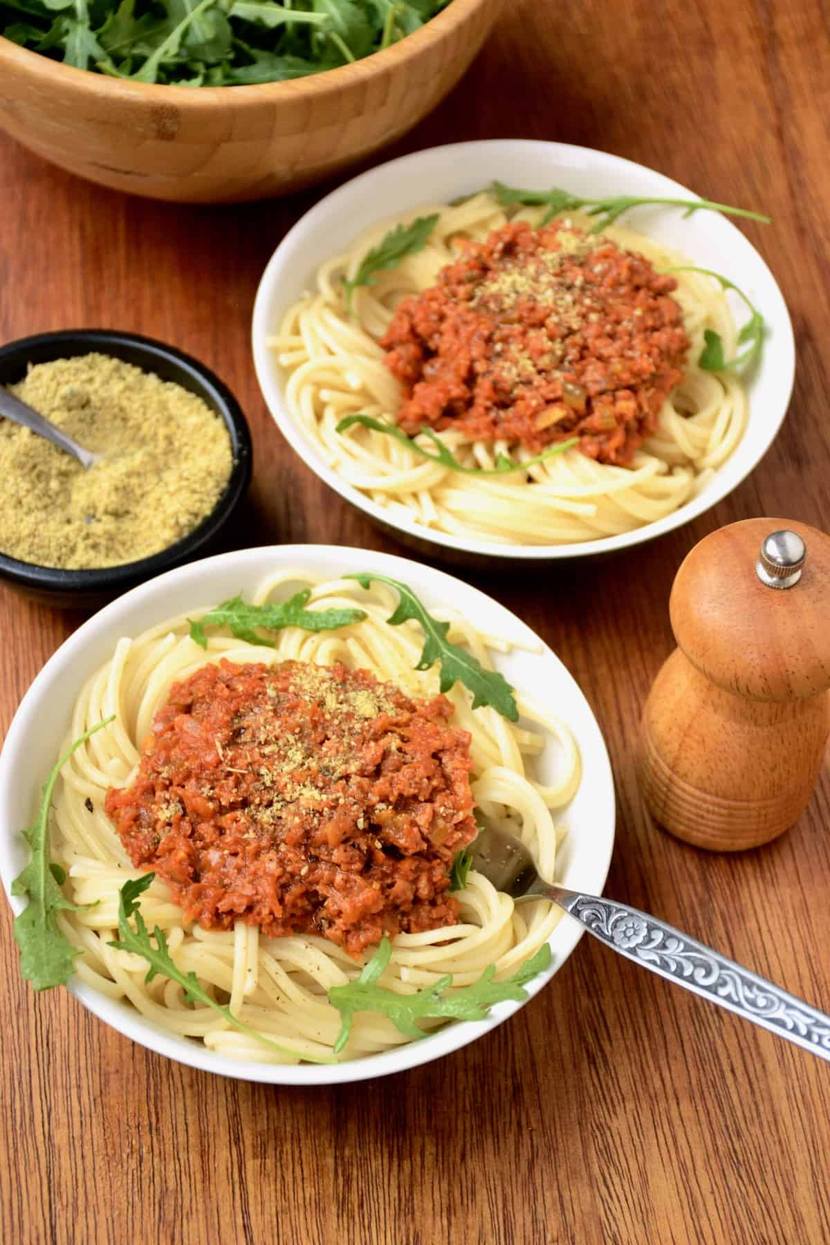 Two potions of pasta with bolognese sauce, a pepper mill and a small bowl of vegan parmesan substitute.