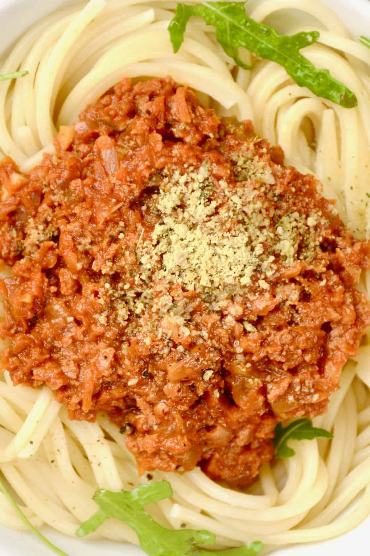 A close up of a bowl of spaghetti bolognese with a sprinkle of finely ground vegan parmesan preparation made from sunflower seeds, nutritional yeast and seasonings...