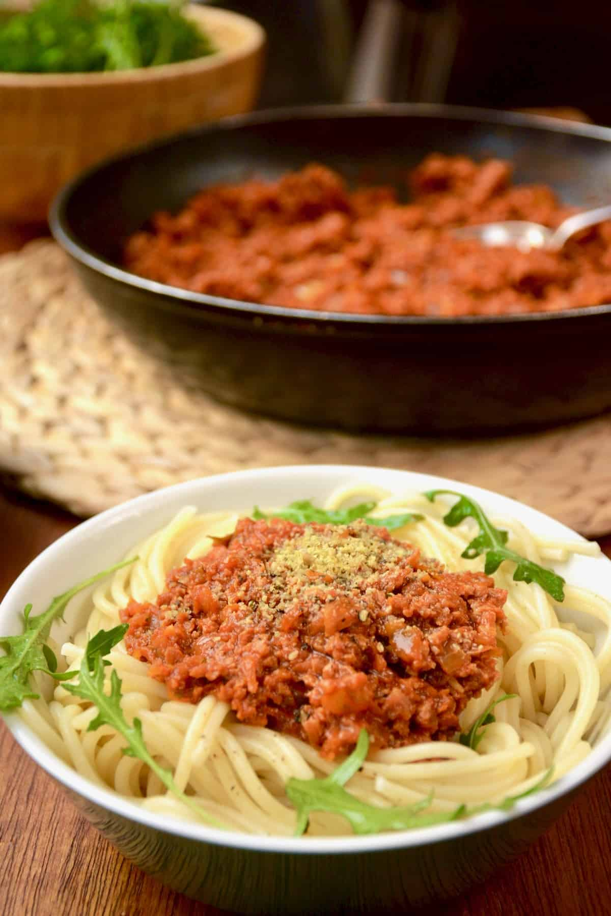 A portion of vegan spaghetti bolognese. In the background a pan full of red ragu and green salad in a wooden bowl.