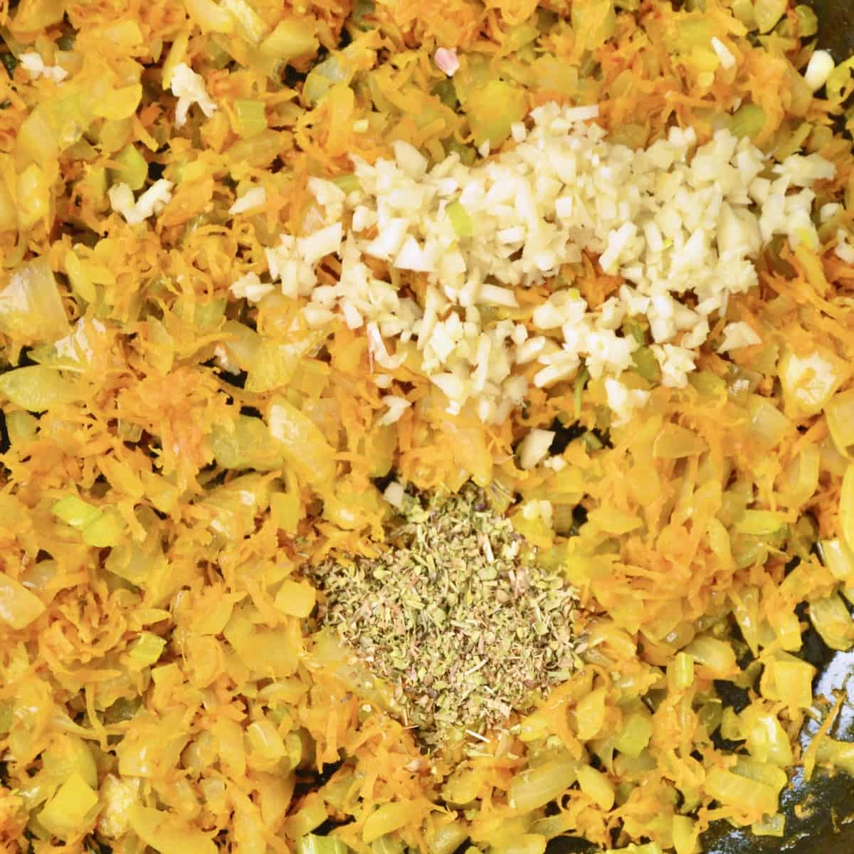Minced garlic and dried herbs added to sauteing vegetables in a frying pan.