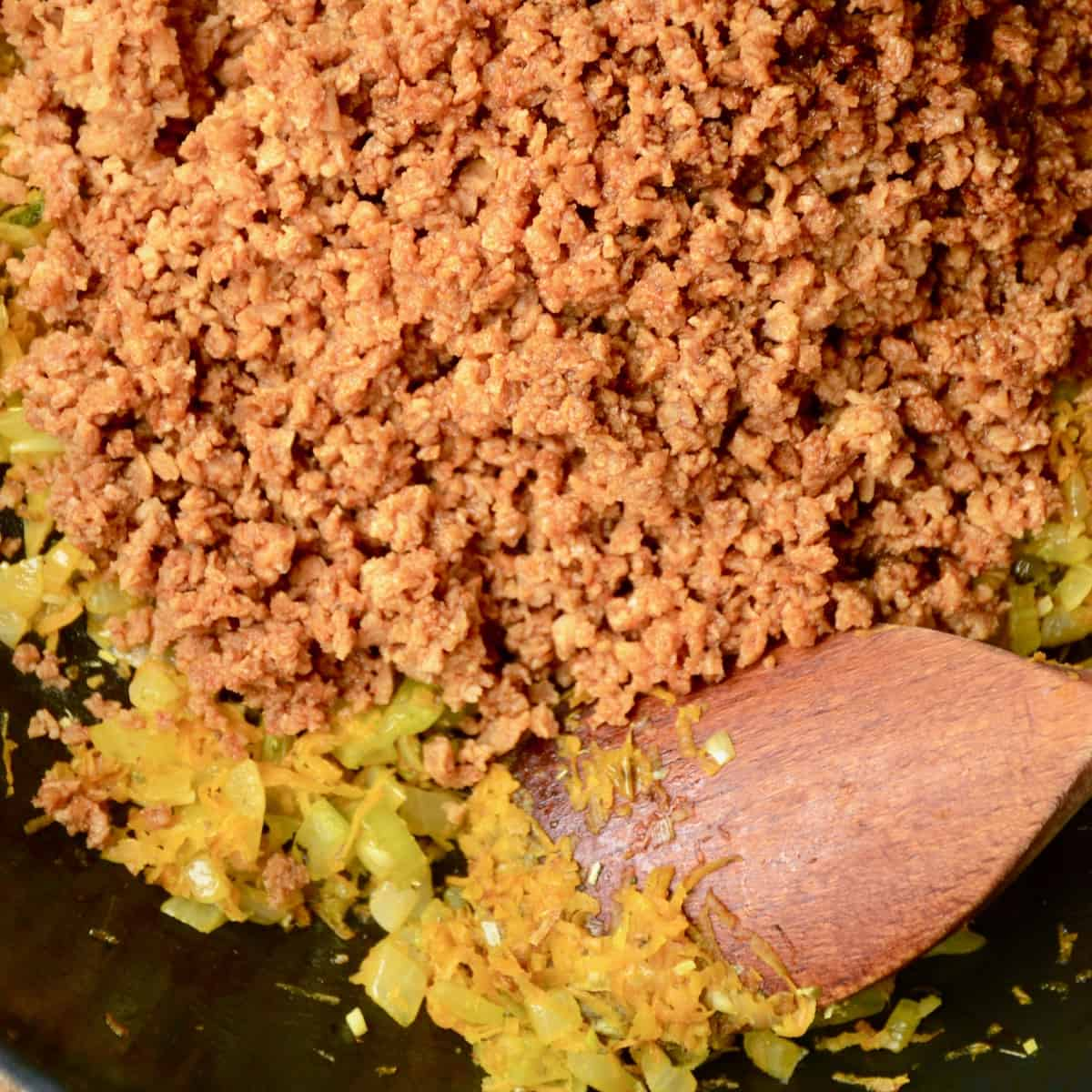 Rehydrated soy mince resembling the look of ground meat is added into the frying pan.
