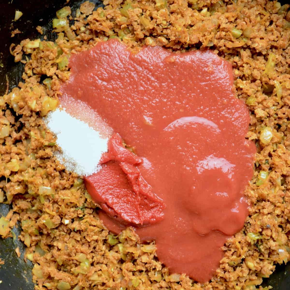 Pureed tomatoes, concentrated tomato paste and some granulated sugar added into the saucepan.